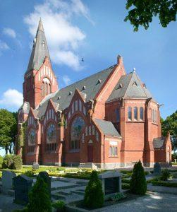 Stor kyrka i rött tegel med grått tak. Gravstenar i förgrunden.
