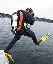 Dykare hoppar i vattnet från båt.