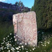 """Runstenen Ög 156 vid Tingstads kyrka i Östergötland vid midsommartid. Texten lyder: """"Tola lät resa stenen efter Torlak, sin son."""" Foto Magnus Källström"""