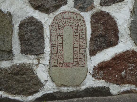 """Runstenen DR 338 i kyrkogårdsmuren vid Glemminge kyrka i Skåne. Slutet av texten lyder: """"Varde till en 'räte' den som bryter (stenen)"""". Vad som menas med 'räte' vet vi inte, men det var förmodligen inget eftersträvansvärt."""