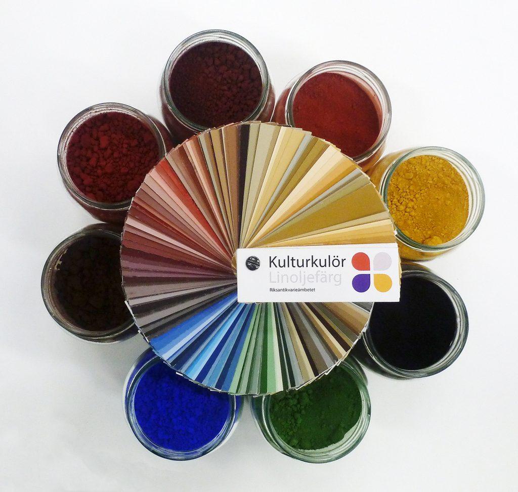 En färgkarta liggande ovanpå färgpigmentburkar