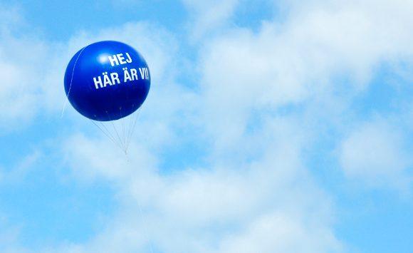 Ballong med texten Här är vi svävar på himlen.
