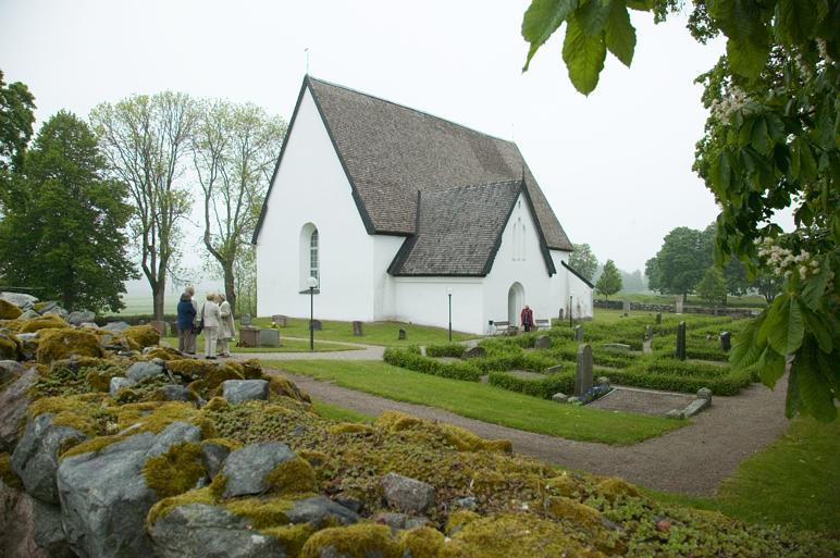 Vit kyrka med grön gräsmatta och stenmur med mossa i förgrunden. Fyra personer står på en grusgång utanför och pratar. Vädret är disigt.