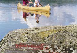 Kanotister i sjön Råvarpen, Dalsland. I förgrunden ses Högsbyns hällristningar.