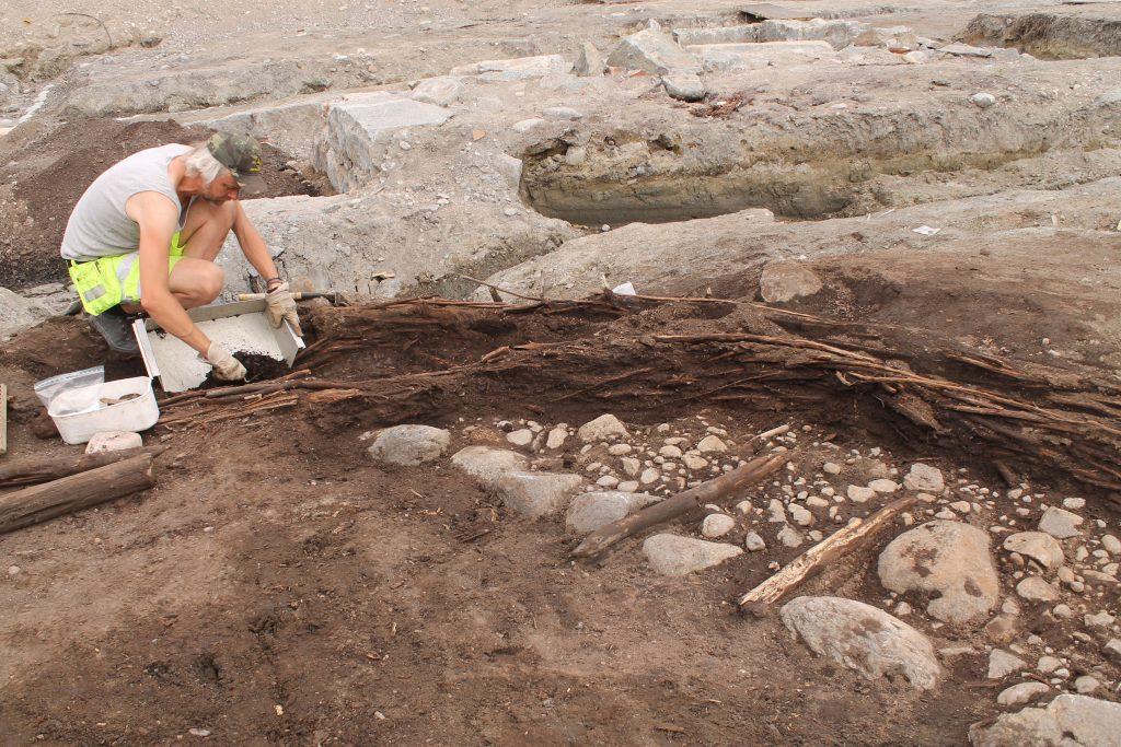 Arkeolog i arbete, på knä framför schackt.