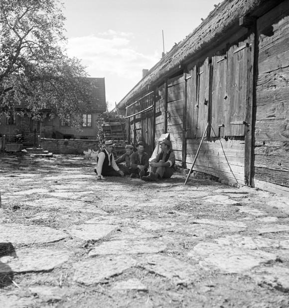 Män som sitter på fägården. I bakgrunden mangårdsbyggnaden till bondgården i Gösslunda, en radby som idag är del av UNESCO:s världsarv Södra Ölands jordbrukslandskap.