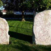 """Runstenarna vid Simris kyrka utanför Simrishamn, DR 345 (t.v.) och DR 344 (t.h.). Den senare är rest till minne av Ravn, som var """"sven hos Gunnulv i Svitjod""""."""