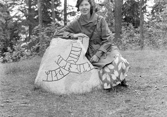 Elisabeth Svärdström vid runstenen på toppen av Björn Järnsidas hög på Munsö utanför Stockholm någon gång i början av 1940-talet. Foto: Dalarnas museums bildarkiv.