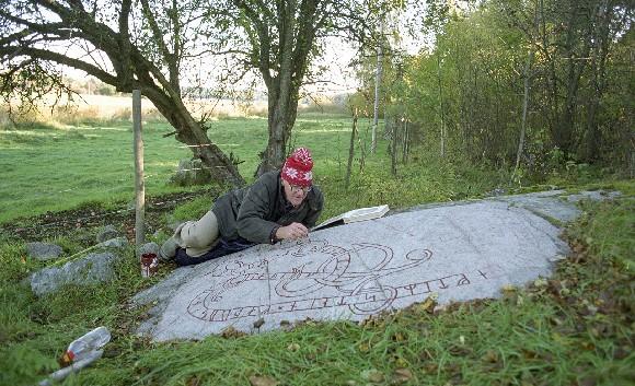 Imålning av runor på runhäll U 145 Fällbro i Täby i Uppland.