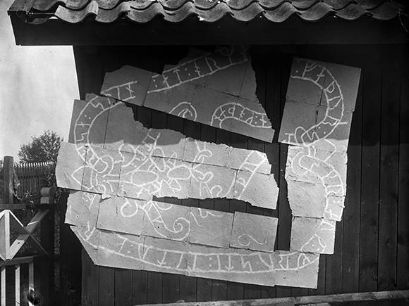 Den då nyfunna runstenen Sö 22 från Håga på Mörkö i Södermanland, som Brate undersökte den 31 juli 1901. Eftersom stenen var söndersprängd i flera delar kunde han inte fotografera fragmenten tillsammans utan valde i stället att göra avklappningar av ristningen och fotografera dessa uppspikade på en husvägg. Foto Erik Brate 1901 (ATA).