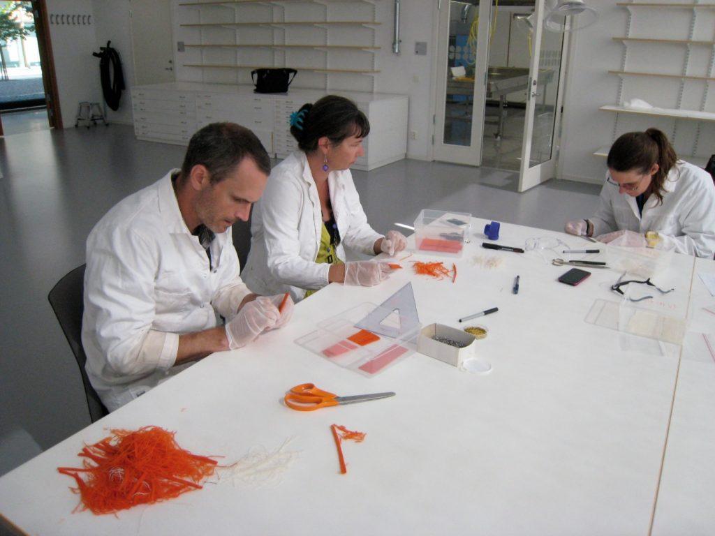 Tre personer sitter i vita laboratorierockar runt ett bord och pillar med textilfibrer för testerna.