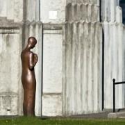 Staty av en människa framför en äldre byggnad