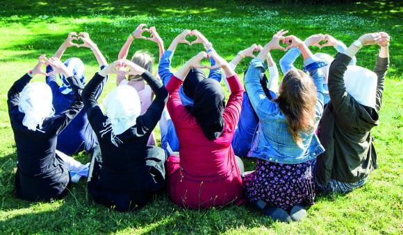Unga flickor sitter med ryggen till och formar hjärtan med händerna