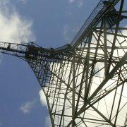 En av radiomasterna i världsarvet Grimeton fotograferad underifrån mot en blå himmel med ett par moln