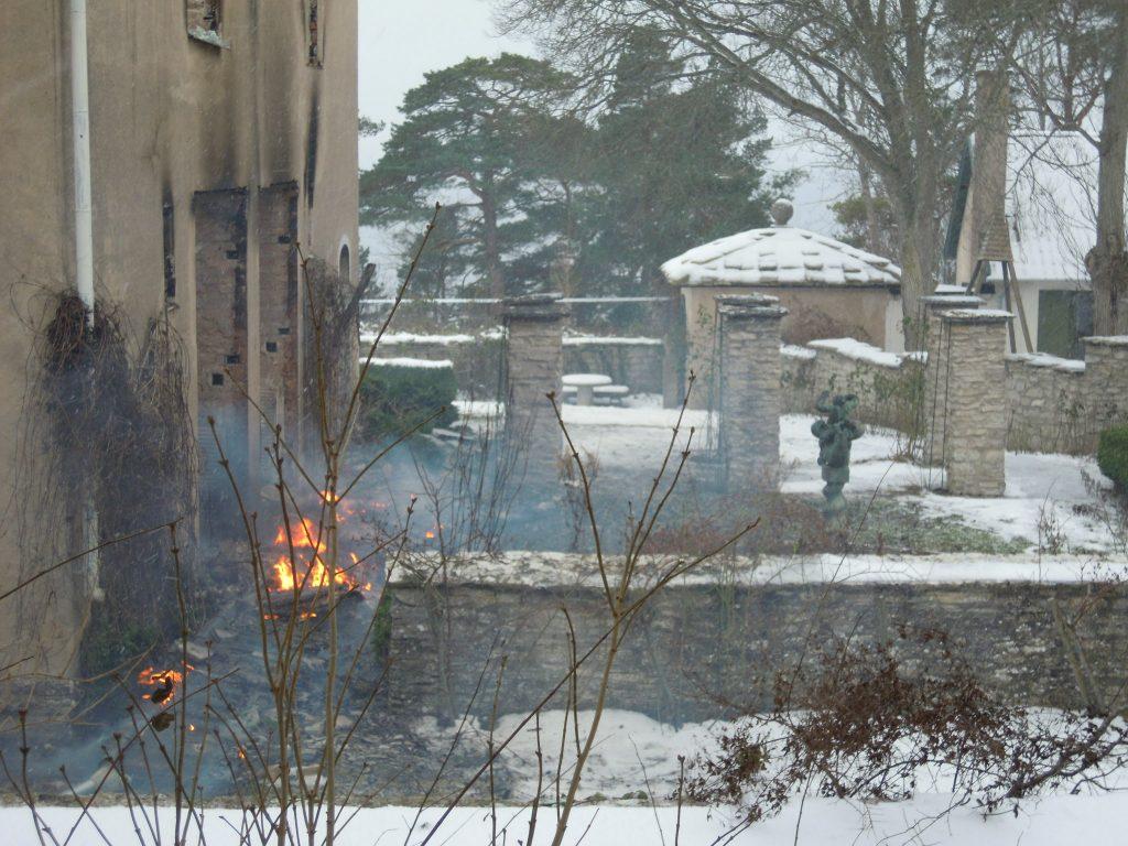 Stenhus med trädgård som har skadats av brand.