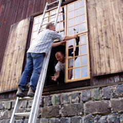 Två personer renoverar ett fönster. En står på en stege och den andra tittar ut och handräcker.