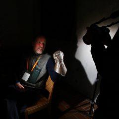 En man håller en kopia av en handske från en medeltida rustning. Siluetten av fotografen och kameran skymtar till höger.