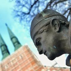 Närbild på staty med kyrkans torn i bakgrunden.