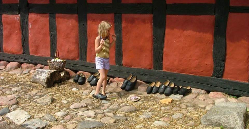Ung flicka framför husvägg på gård med kullerstenar provar skor i alla möjliga storlekar.