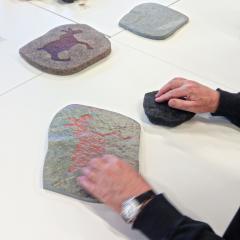 Medlemmar i Synskadades Riksförbund undersöker den taktila tillgängligheten hos modeller och kopior av hällristningar från Nämforsen. Till vänster en 3D-utskrift i skala 1:1 av en hällristning från Nämforsen, och till höger en kopia i sten av samma ristning i 50% skala.