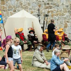 Medeltidsklädda besökare och turister pausar framför borgen.