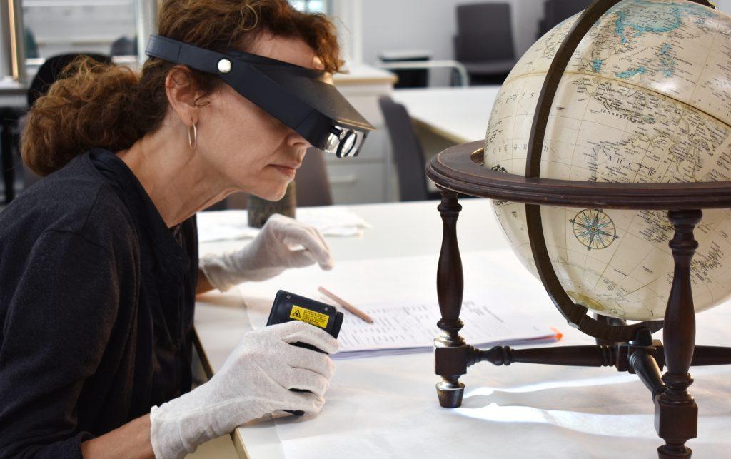 Person med förstoringsglasögon och ficklampa undersöker en jordglob.