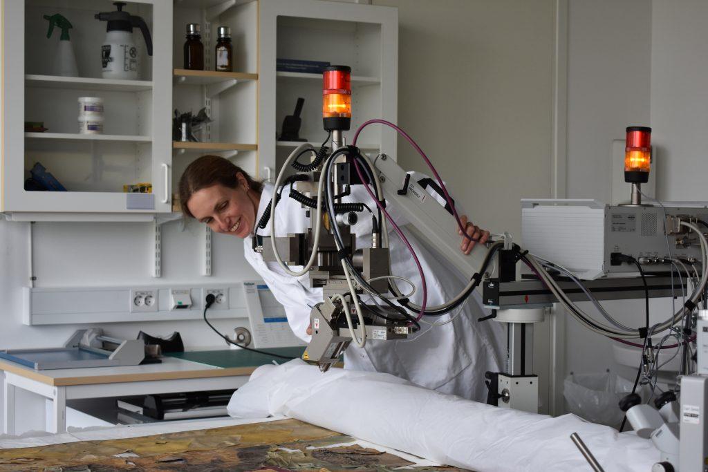 Marei Hacke på Kulturarvslaboratoriet undersöker en av fanorna med hjälp av XRF (röntgenfluorescensteknik).