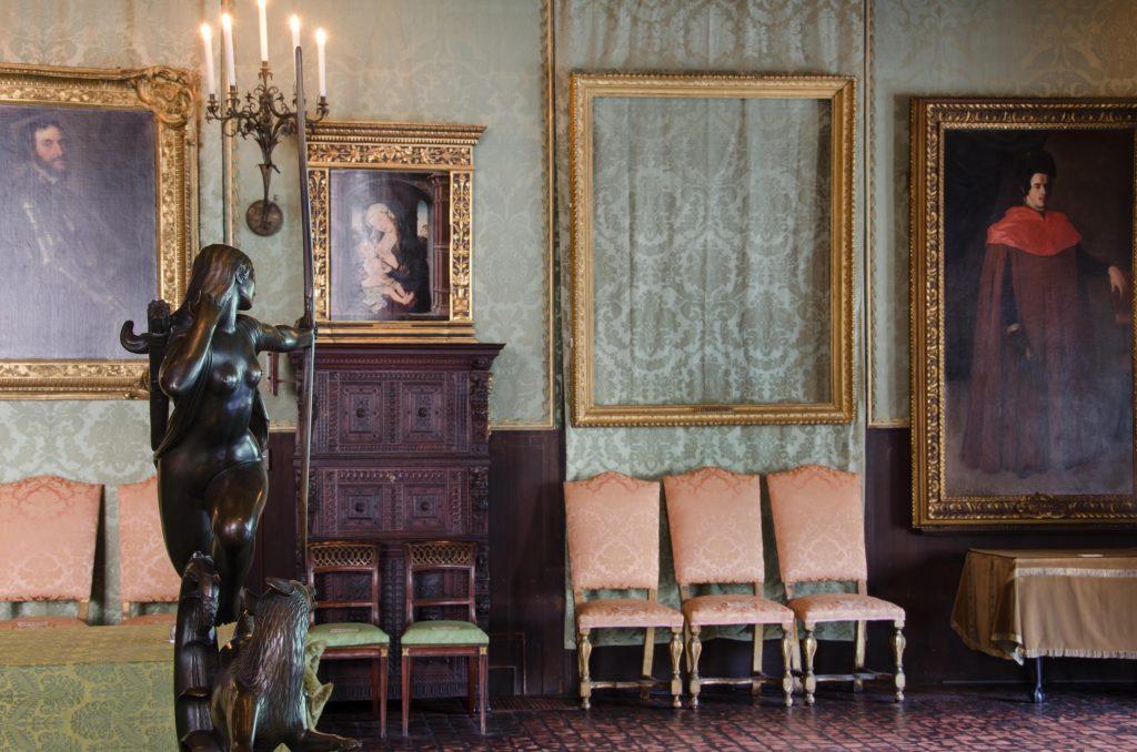 Ett rum med stora tavlor i guldram på väggarna. En stor staty står mitt på golvet.. En av de stora förgyllda ramarna är tom.