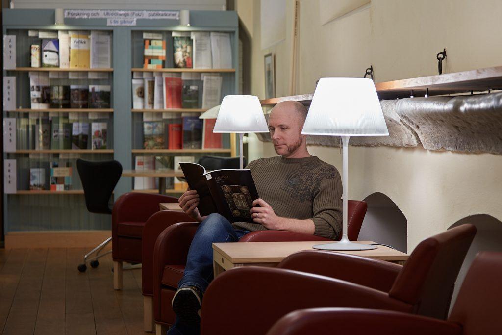 Man sitter och läser i biblioteket