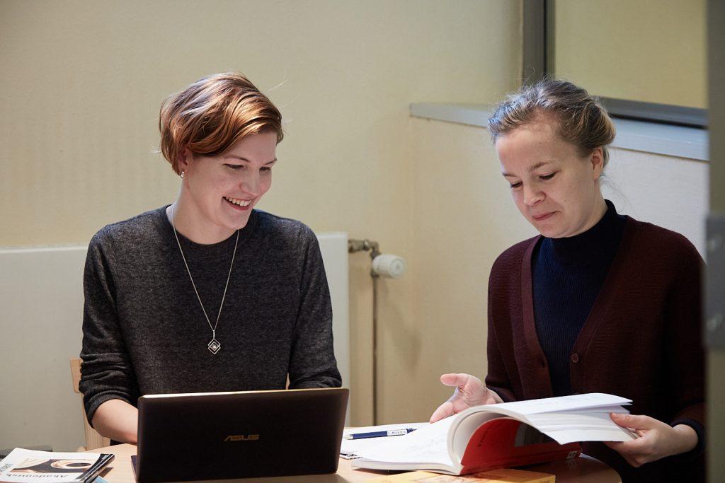 Två kvinnor läser vid ett bord