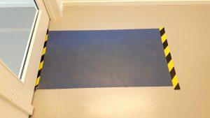 Blå klibbig matta framför dörröppning för att fånga upp smuts och skadedjur, fungerar som en postit-lapp, man drar av ett lager i taget tills det blir mättat med smuts.