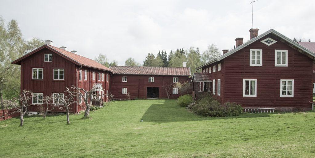 Exteriör med tre stycken ädre hus med röd träpanel står i en vinkel.