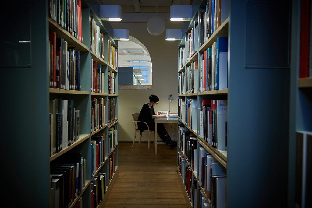 Kvinna som läser i biblioteket
