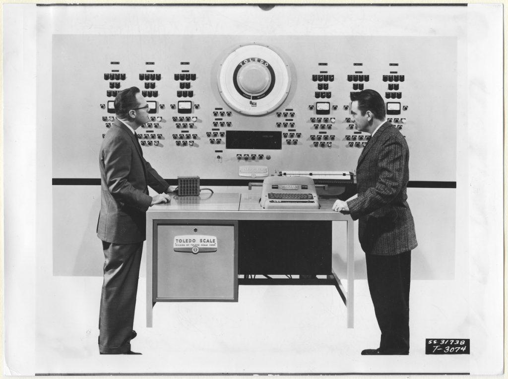 Svartvitt foto med två personer som möts i ett datorrum.