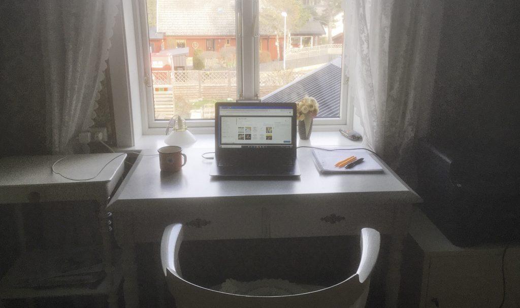Hemmakontor med dator på skrivbord och fönster med utsikt över trädgård