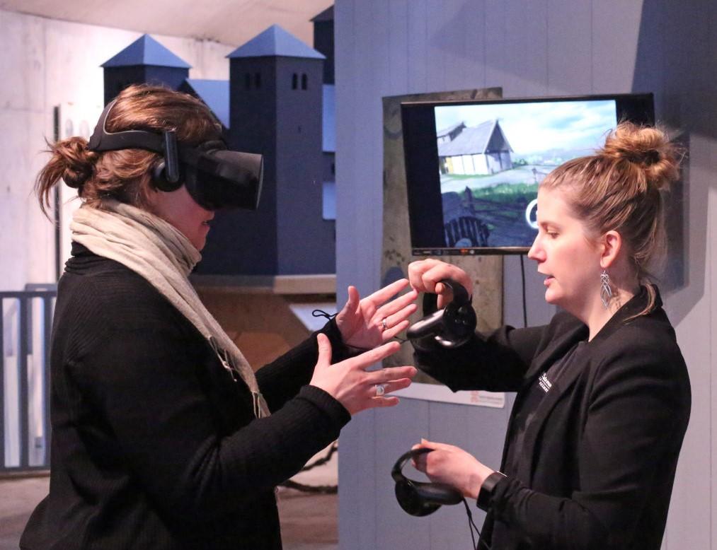 Två personer i en muséelokal framför en tv-skärm. Den ena personen har VR-glasögon på.