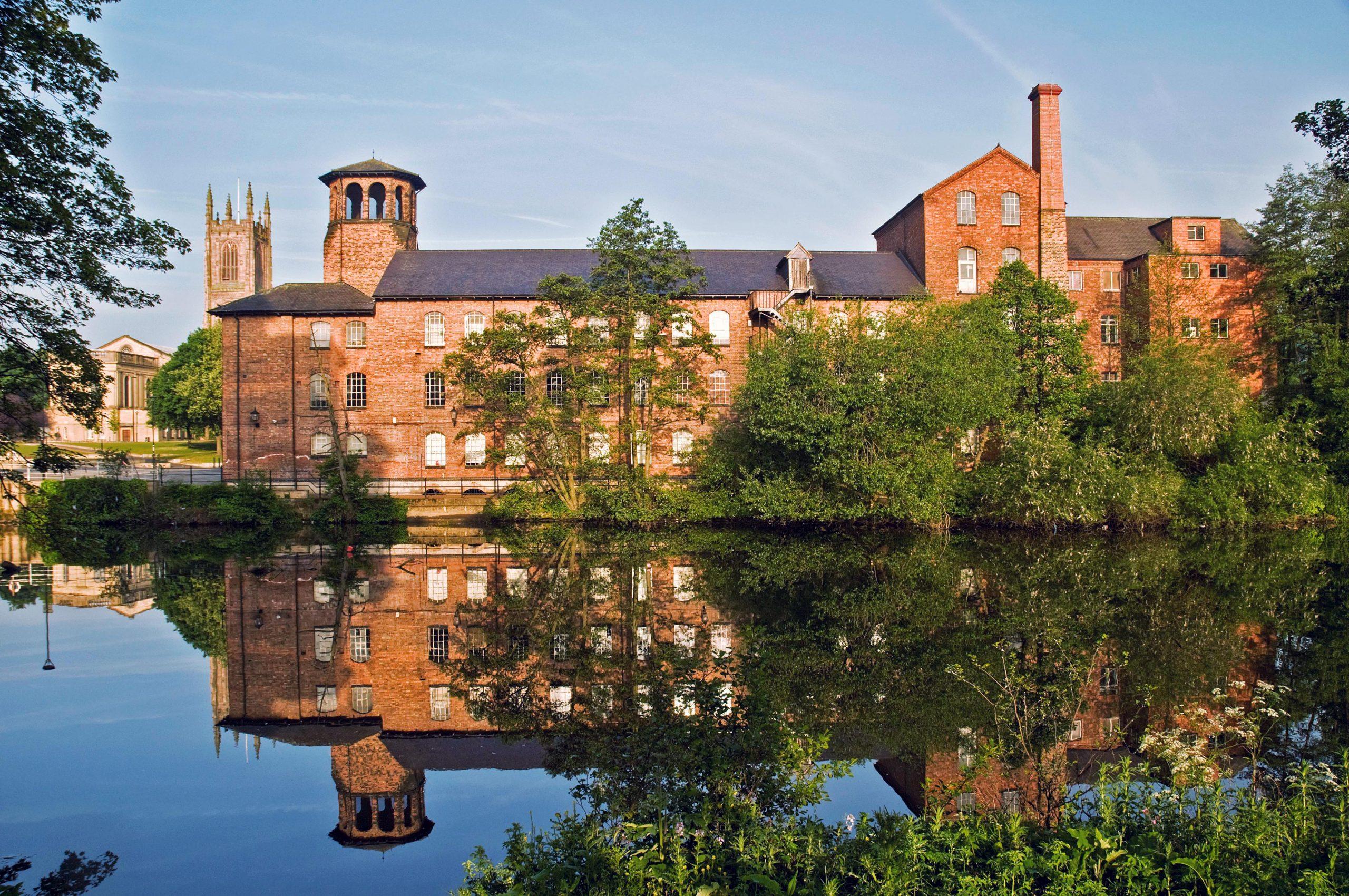 En stor byggnad i rött tegel med en identisk spegelbild i floden framför.