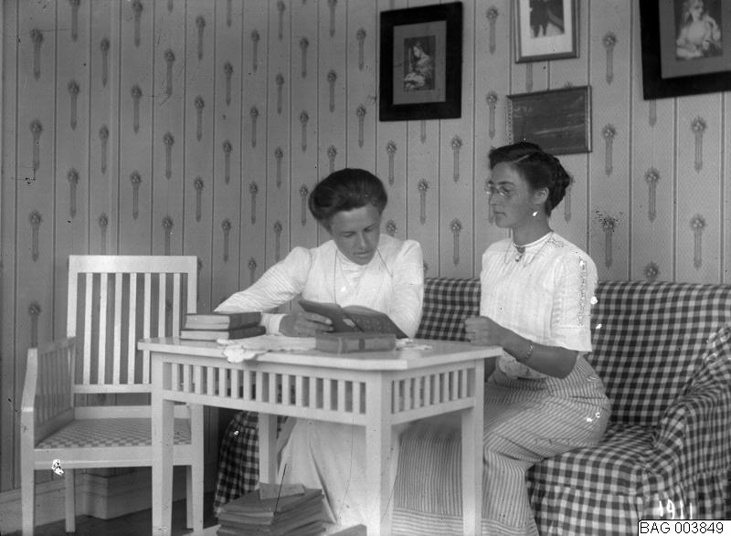 Rumsbild, två kvinnor vid bord, läsande. 1911.