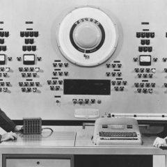 Svartvit bild med två män som möte i ett datorrum.