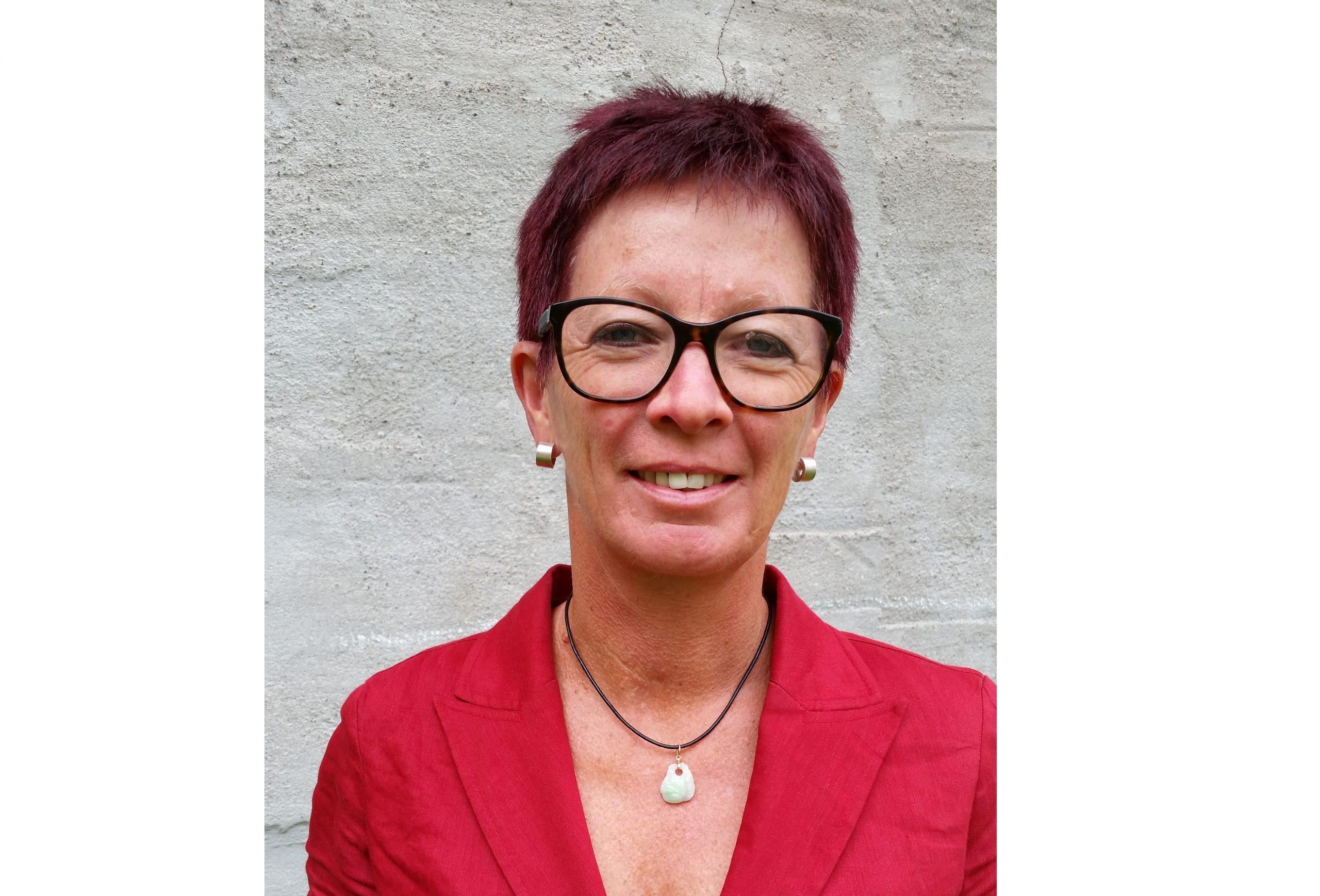 Porträtt på Liv Ramskjær, generalsekreterare för Norges museumsförbund. Hon är klädd i rött och bär glasögon med mörka bågar.