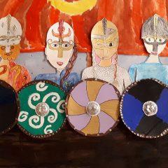 Barnteckning föreställande ett vikingaskepp med hissat segel och sköldar i olika mönster.