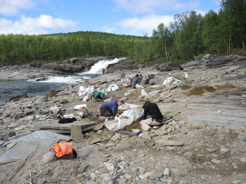 Människor på arkeologisk utgrävningsplats nära en fors