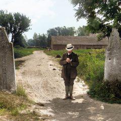 Man med hatt och block i handen står framför medeltida grindstolpar med runor på.