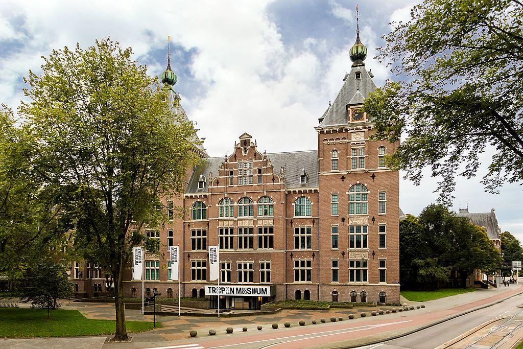Äldre tegelbyggnad med två torn. På framsidan flaggor med texten Tropenmuseum.