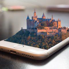 En stad som växer fram ur en mobiltelefon som ligger ner på en bordsskiva.