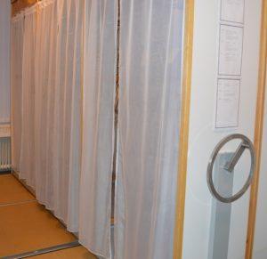 Kompaktaskåp med hyllorna täckta av vita hängande tygstycken