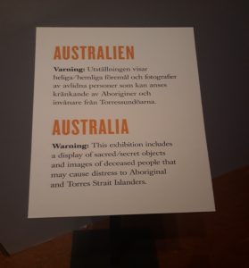 Skylt med texten Varning: Utställningen visar heliga/hemliga föremål och fotografier av avlidna personer som kan anses kränkande av Aboriginier och invånare från Torressundöarna.