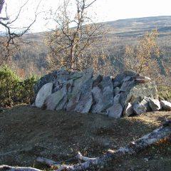 Samisk grav med staplade stenar i fjällandslkap