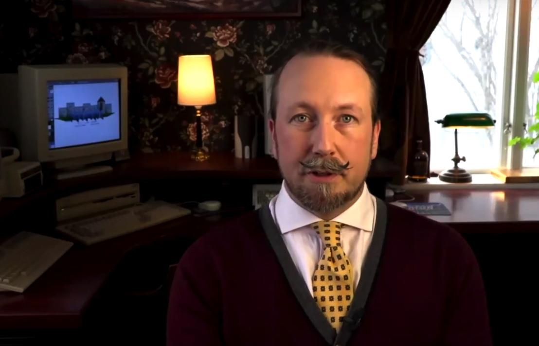Fredrik i mörk kavaj och gul slips.