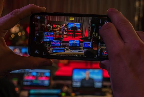 Foto taget på en mobiltelefon som i sin tur fotar en liveinspelning. En person i studion och en person som medverkar via skärm. I Mobilen kan man se flera bildskärmar.